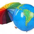 Big inflatable globe and colored umbrella isolated on white back - Stock Photo