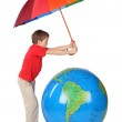 Boy in red shirt with multicolored umbrella and inflatable globe — Stock Photo #7938604