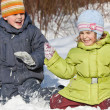 Boy and little girl play sitting in snow in winter in wood — Stock Photo #7938621