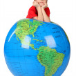Boy in red shirt leans on inflatable globe chin on hands isolat — Stock Photo #7938624