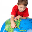 Boy in red shirt leans on inflatable globe isolated on white bac - Stockfoto