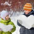 Teenager boy and little girl keeps in hands hearts from snow in — Stock Photo