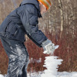 Stock Photo: Boy creates pyramid from ice in sunny day in winter in wood, Un
