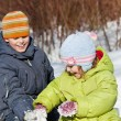 Boy and little girl play sitting in snow in sunny day in winter — Stock Photo #7938694