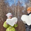 Boy and little girl keeps in hands hearts from snow in winter in — Stock Photo