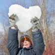 Boy keeps in hands hearts from snow over head in winter in wood — Stock Photo