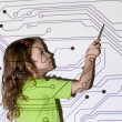 Pretty little girl shows pointer on electric scheme throw projec - Stock Photo