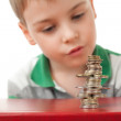 Boy in striped T-shirt looking at curve pile from coins coins — Stock Photo #7938828