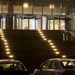 Grand entrance in modern office building at night, two cars on p - Stock Photo