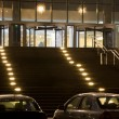Grand entrance in modern office building at night, two cars on p — Stock Photo