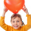 Laughing little girl holds over her head heart shape balloon iso — Stock Photo #7938950