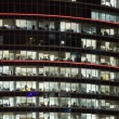 Modern office building with big windows at night, in windows lig — Stock Photo