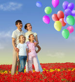 Family of four in red field and balloons collage — Stock Photo