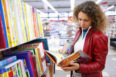 Beautiful girl in red jacket thoughtfully considers children's book in bookshop. — Stock Photo