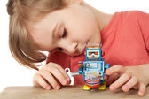 Little girl in red T-shirt plays with clockwork robot isolated o — Stock Photo