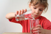 Little girl in red shirt pour out water from one glass to other, — Stock Photo