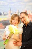 Uomo in bicchieri abbracciando la ragazza di bellezza bionda con bouquet di fiori, — Foto Stock