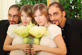 Man in glasses and beauty blond girl with flowers bouquet standi — Stock Photo