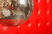 Dance mirror ball on red leather background — Stock Photo