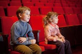 Boy and little girl sitting on armchairs at cinema — Stock Photo