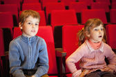 Boy and little girl sitting on armchairs at cinema, girl has op — Stock Photo