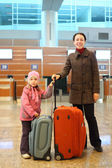 Young mother and little girl with suitcases standing at airport — Stock Photo