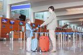 Ojciec i syn z czerwoną walizkę stoi w hali lotniska stronie v — Zdjęcie stockowe