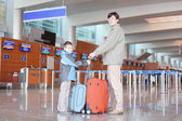 Father and sonl with red suitcase standing in airport hall side — Stock Photo