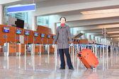 红色行李箱站在机场大厅里的女孩 — 图库照片