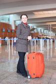 Flicka med röd resväska står i flygplatsen hall och ler — Stockfoto