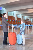 Mother and son with suitcases standing in airport hall side view — Stock Photo