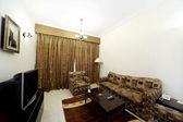 Sala com cortina marrom do sofá, poltronas e tv fechada — Foto Stock