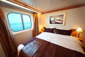 Ship cabin with big double bed and window with view on sea summe — Stock Photo