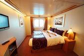 Kleiner junge liegt am großen doppelbett im schiff kabine gesamtansicht summe — Stockfoto