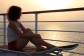 Dziewczyna siedzi na krześle plaży na pokład statku i patrząc na di — Zdjęcie stockowe