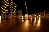 Empty cruise ship deck with beach chairs and lamps at night time — Stock Photo