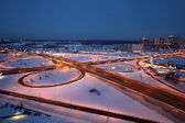 Night winter cityscape with big interchange and lighting columns — Stock Photo