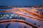 Evening winter cityscape with big interchange and lighting colum — Stock Photo