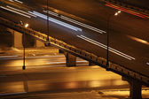 Night city with bridge and lighting columns road traffic with tr — Stock Photo