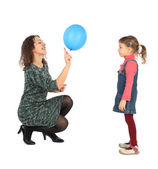 Little girl and her mother playing with blue balloon side view i — Stock Photo