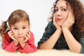 Little girl and her mother lies on white fell, hands on chin,loo — Stock Photo