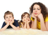 Mother with two serious children lies on white fell studio shoot — Stock Photo