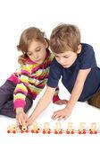 Kleine jungen und mädchen spielen mit holzschienenbahn sitzen auf boden — Stockfoto