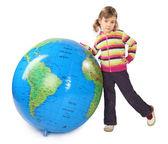 Liten flicka står nära stor uppblåsbar jordglob, stöttes ut en l — Stockfoto