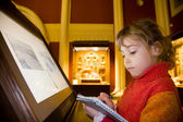 Little girl standing near monitor writes to writing-books at exc — Stock Photo