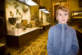 Boy at excursion in historical museum near exhibits of ancient r — Stock Photo