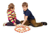 Little boy and girl playing with wooden railway sitting on floor — Stock Photo