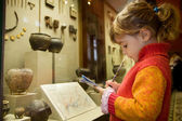 Little girl writes to writing-books at excursion in historical m — 图库照片