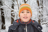 Smiling boy in cap in wood in winter — Stock Photo