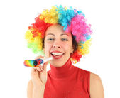 Young beauty woman in clown wig and with party blower, laughing — Stock Photo